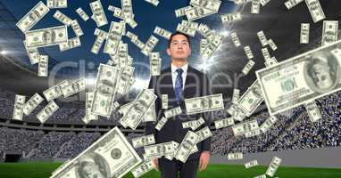 Money falling on businessman at football stadium representing corruption