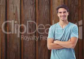 Happy young man standing arms crossed against wooden wall