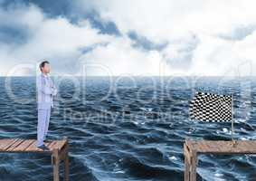 businessman with his hands folded looking to the checker flag in a quay