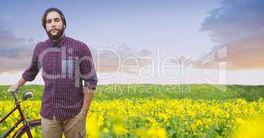 Male hipster with bicycle on flowering field