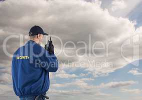 Rear view of security guard using radio against cloudy sky