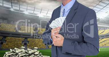 Midsection of businessman hiding money at soccer stadium representing corruption concept