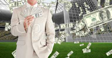 Midsection of businessman showing money at football stadium representing corruption