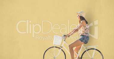 Side view of woman riding cycle over beige background