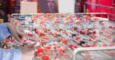 Hands taking picture of shopping carts with transparent device in store