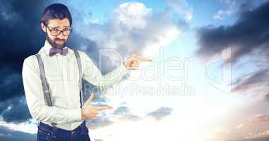 Male hipster pointing against cloudy sky