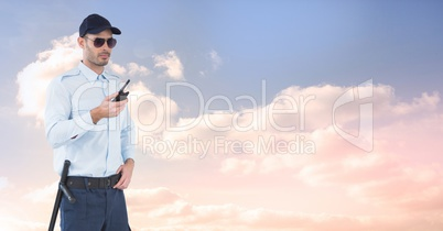 Security guard holding radio against sky