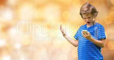 Angry boy holding mobile phone over blurred background