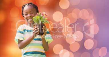 Portrait of happy boy holding flower pot over bokeh