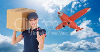 Delivery woman with parcel gesturing thumb up against airplane flying in sky