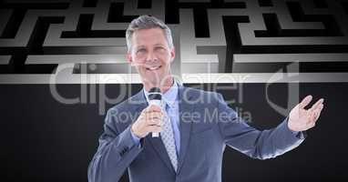 Confident businessman holding microphone against maze