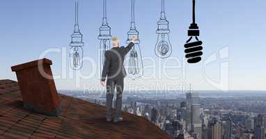 Businessman drawing various lighting equipment while standing on roof