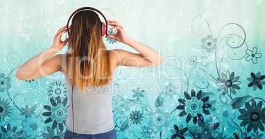 Rear view of woman listening to songs on headset against floral pattern