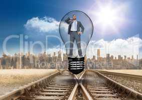 Digital composite image of businessman in light bulb over tracks