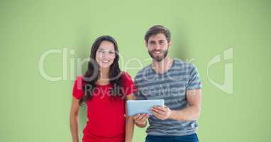 Portrait of male and female hipsters with digital tablet against green background
