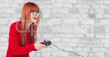 Happy female hipster playing video game against wall