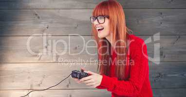 Redhead woman playing video game against wooden wall