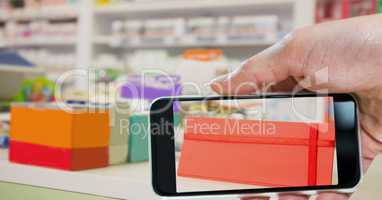Hand taking picture of envelope with smart phone in store