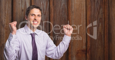Portrait of successful businessman clenching fists against wooden wall