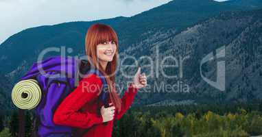 Portrait of happy female traveler showing thumbs up against mountain