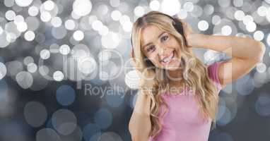 Happy woman listening to songs on headphones against bokeh