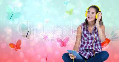Happy female listening to music through headphones using tablet PC over butterfly background