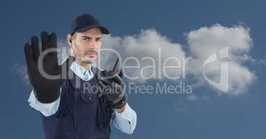 Security guard using radio while showing stop gesture against sky