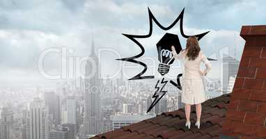 Rear view of businesswoman on roof drawing light bulb in midair