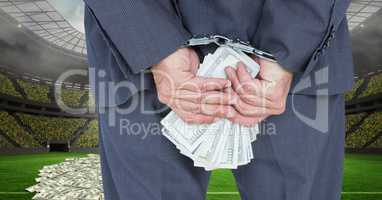 Midsection of businessman with handcuffs and money at football stadium representing corruption