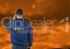 Rear view of security guard against cloudy sky during sunset