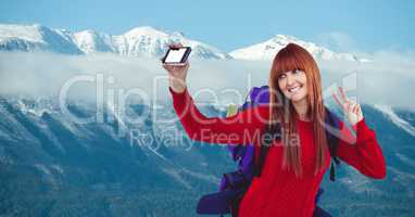 Happy female hiker taking selfie through smart phone against snow covered mountain