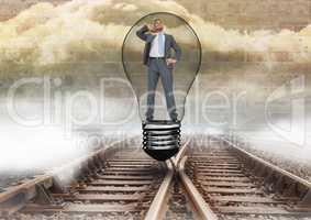 Businessman in light bulb over tracks
