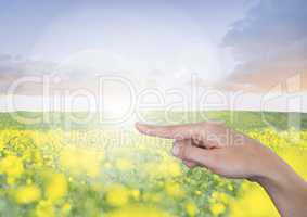Hand pointing in  air of  flower meadow and blue sky