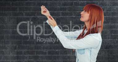 Side view of redhead woman with arms raised against wall