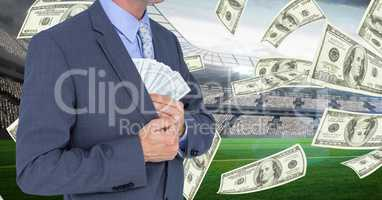 Midsection of businessman hiding money in blazer at football stadium representing corruption