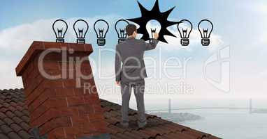 Businessman drawing lighting equipment while standing on roof