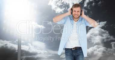 Smiling man listening to songs on headphones against sky