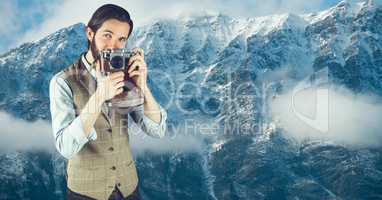 Hipster man photographing against snowcapped mountains