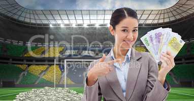 Smiling businesswoman showing money at stadium representing corruption
