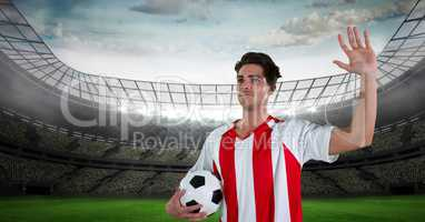 Soccer player with arm raised holding ball in stadium