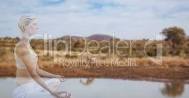 Double exposure of woman meditating by lake