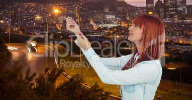 Redhead woman with arms raised in city