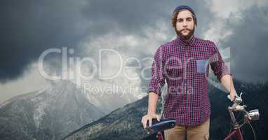 Portrait of confident male traveler holding bicycle on mountain