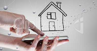 Hands using mobile phone against drawn house