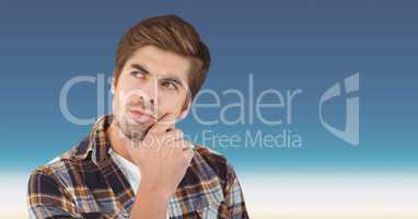 Thought male hipster with hand on chin against sky