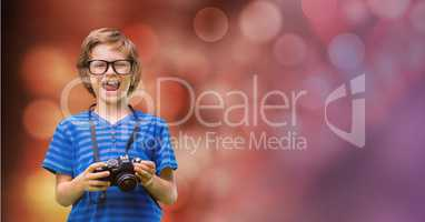 Little boy holding camera while laughing