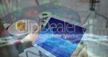 Digital composite image of businesswoman's hands holding tablet PC with graph on screen