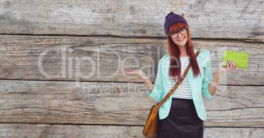 Female hipster holding clutch while gesturing against wooden wall