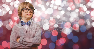 Smart boy standing with arms crossed over bokeh