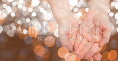 Close-up of cupped hands against glowing bokeh